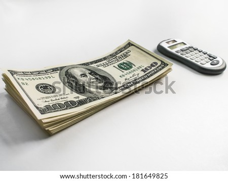 American US dollars and calculator on a white background - stock photo
