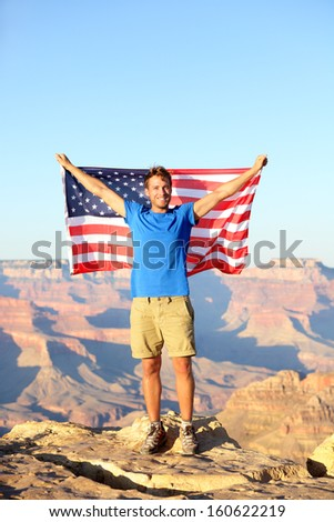 American USA flag - tourist in Grand Canyon. Happy young man hiking and cheering at Grand Canyon south rim during summer holidays in the United States. Young male hiker in his 20s. - stock photo