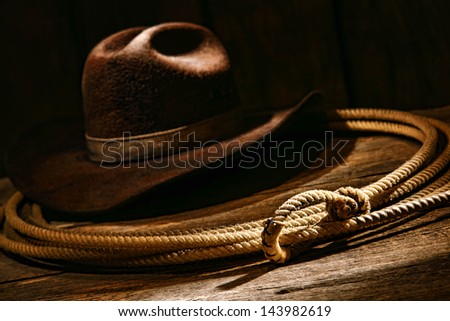 American West authentic rodeo cowboy lariat lasso honda noose with end loop rawhide speed burner on weathered aged barn wood plank with vintage brown felt hat - stock photo