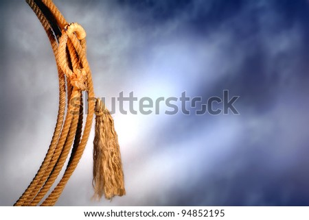 American West authentic rodeo cowboy lariat lasso hondo or honda noose with end loop rawhide speed burner detail and tassel over dramatic stormy sky - stock photo