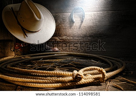 American West authentic rodeo cowboy lariat lasso with end loop rawhide speed burner on aged barnwood floor with straw hat atop western boots in an old wooden ranch barn in soft and diffused sunlight - stock photo
