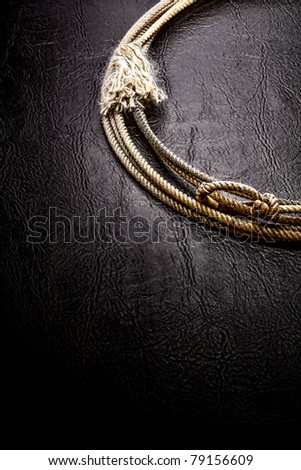 American West authentic vintage rodeo cowboy lariat lasso on grunge black leather surface background