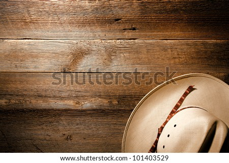 American West authentic white straw cowboy hat on old and aged western saloon floor wood plank background - stock photo