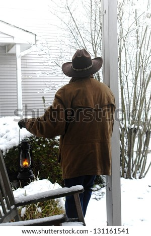 American West legend cowboy with western hat and leather jacket on a cold ranch front porch holding a lit kerosene lantern while contemplating new falling snow in winter weather - stock photo