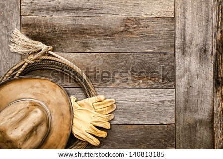 American West legend old and dirty tan cowboy hat and pair of working rancher gloves atop a lasso lariat rope on an old wood boards barn floor in a vintage ranch barn - stock photo
