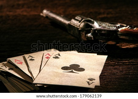 American West Legend poker game stack of cards with four aces on top and gambler revolver gun on a wood table in an old western gambling saloon scene on the old frontier - stock photo