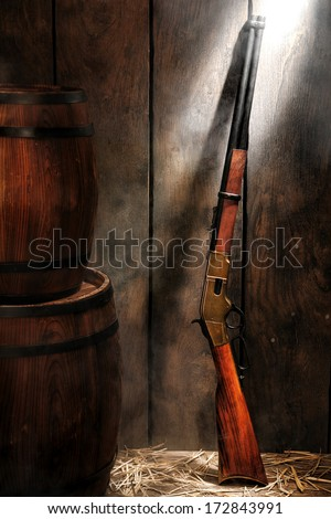 American West legend repeating lever action rifle antique western gun and wood aged provision barrels in an old reserve stockroom with distressed wooden wall with light smoke - stock photo