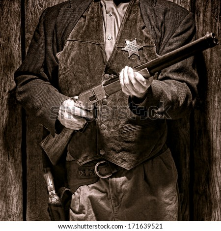 American West Legend sheriff deputy holding a rifle at ready to protect a western town peace and safety as mandated by law  - stock photo