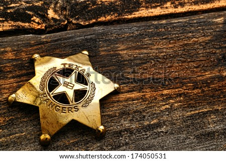 American West Legend Texas Ranger lawman antique justice symbol brass badge with old Lone Star state flag engraving used by frontier law enforcement deputy on wet weathered wood - stock photo