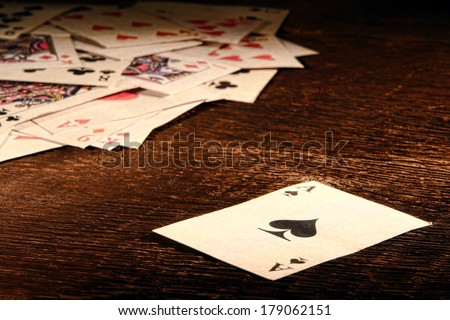American West Legend vintage ace of spade playing card and stack of antique poker game cards on a weathered wood table in an old western frontier gambling establishment saloon - stock photo