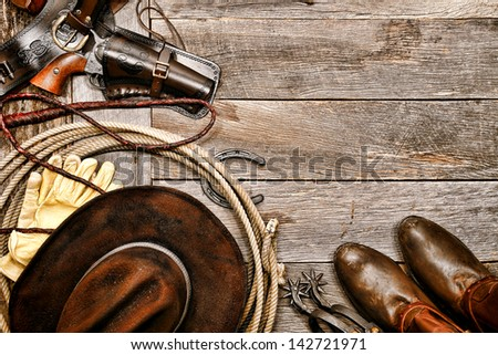 American West legend western cowboy ranching gear still life with old revolver gun in leather holster along lariat lasso and antique hat near boots and spurs on wood board ranch barn floor background - stock photo