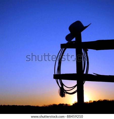 American West rodeo authentic cowboy hat and lariat lasso hanging on a ranch fence post in backlit silhouette over blue sky at sunset - stock photo