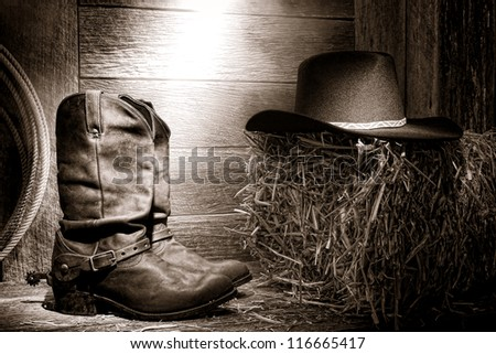 American West rodeo authentic leather roper boots and traditional western black felt hat on a bale of straw