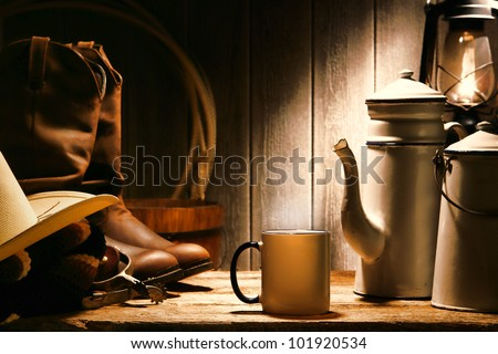 American West rodeo cowboy authentic working gear with genuine hat and leather rancher boots on an old wood table with vintage cup and steel enamel pot of coffee for a break in an antique ranch barn