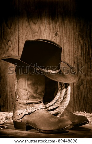 American West rodeo cowboy black felt hat atop worn western boots and spurs with old ranching rope in an antique wood barn in nostalgic vintage sepia - stock photo