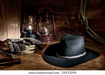 American West rodeo cowboy black felt hat with old burning kerosene oil lamps and authentic traditional rancher tools over wood in a vintage ranch barn