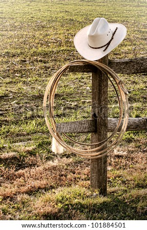 American West rodeo cowboy hat and authentic lariat lasso hanging on a ranch fence end post - stock photo