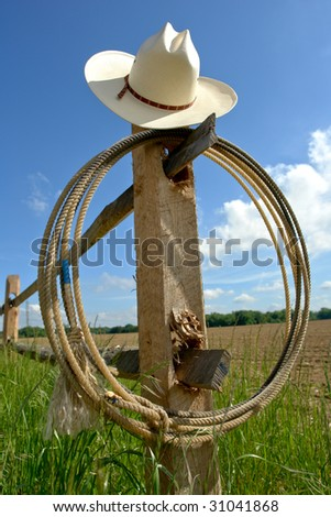 American West rodeo cowboy hat and lasso rope on a wood post fence on a ranch field under blue sky