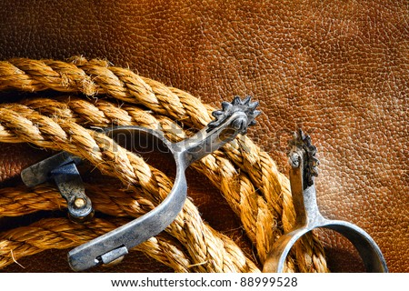 American West rodeo cowboy ranching rope with western riding spurs on old brown leather grunge background - stock photo