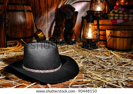American West rodeo cowboy traditional black felt hat on straw covered wood floor in vintage ranch barn with antique ranching supplies and rancher tools lit by old nostalgic kerosene lantern oil lamps - stock photo