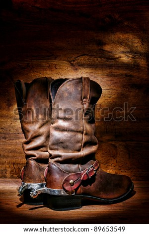 American West rodeo cowboy traditional leather boots with authentic Western riding spurs over vintage wood in a ranching barn - stock photo