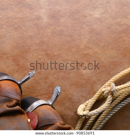 American West rodeo cowboy traditional leather boots with riding spurs and authentic Western lasso lariat with hondo or honda loop on brown leather texture background - stock photo