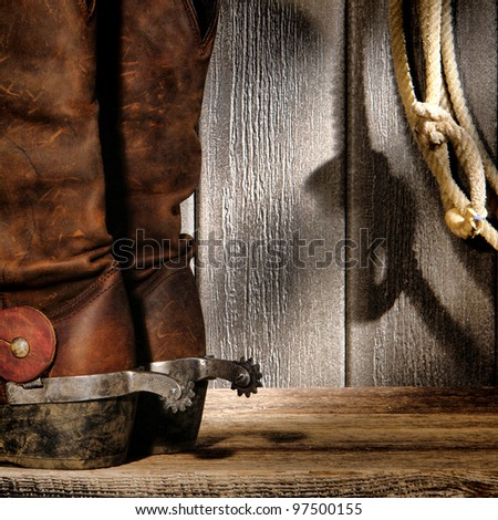 American West rodeo cowboy traditional leather boots with roping riding spurs and authentic Western lasso lariat on weathered barn wood background - stock photo