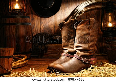 American West rodeo cowboy traditional leather working rancher roper boots with authentic Western riding spurs in a vintage ranch barn with ranching tools lit by old nostalgic kerosene oil lamps - stock photo