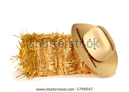 American West rodeo cowboy traditional straw hat over bale of hay straw over white 