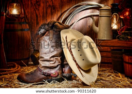 American West rodeo cowboy traditional white straw hat on leather rancher roper boots with authentic Western riding spurs in vintage ranch barn with antique ranching supplies lit by kerosene lantern - stock photo