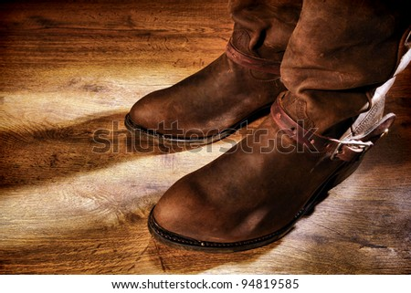American West rodeo cowboy traditional working ranching boots with old leather Western riding spur straps on distressed grunge wood floor - stock photo
