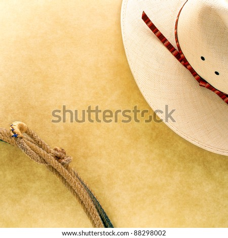 American West rodeo cowboy white hat and authentic Western lariat style lasso with hondo loop on smooth grunge leather texture background - stock photo
