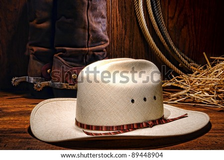 American West rodeo cowboy white hat with western boots and spurs on wood with lasso lariat and straw in a ranching barn - stock photo