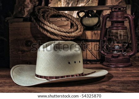 American West rodeo cowboy white straw hat with traditional ranch equipment and old ranching tools in a nostalgic Western barn 