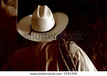 American west rodeo cowboy with white hat and lasso rope on his shoulder viewed from back in nostalgic sepia 
