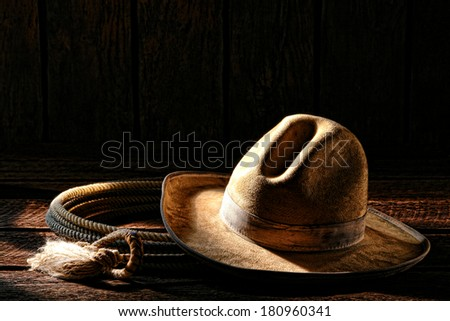 American West rodeo cowboy worn and dirty white felt hat with authentic roping lariat lasso old weathered wood planks in an old western ranch wooden barn in morning light  - stock photo