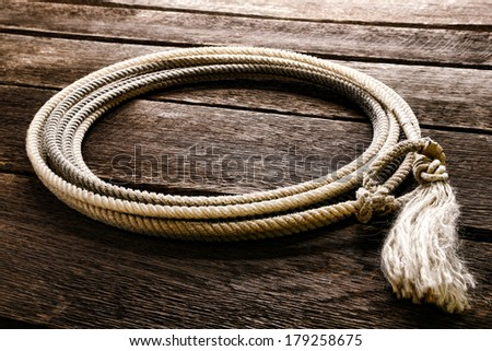 American West rodeo genuine cowboy lariat lasso with honda noose loop over rawhide speed burner and end tassel on vintage weathered barn wood planks in a western ranch - stock photo