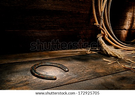 American West rodeo rusty old forgotten western horseshoe on ranch barn wood floor with lasso lariat on antique wooden wall   - stock photo