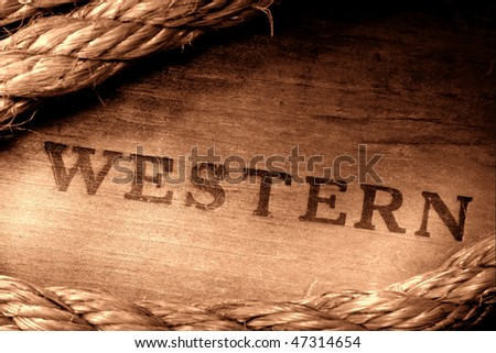 American West rodeo title word Western stamped branding on grunge wood board with old rope frame