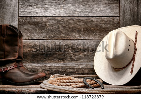 American West rodeo traditional white straw cowboy hat with authentic Western lariat lasso and roper leather boots on distressed barn wood background - stock photo