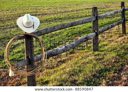 American West rodeo vintage cowboy hat and authentic lariat lasso hanging on a ranch fence post near a prairie field - stock photo