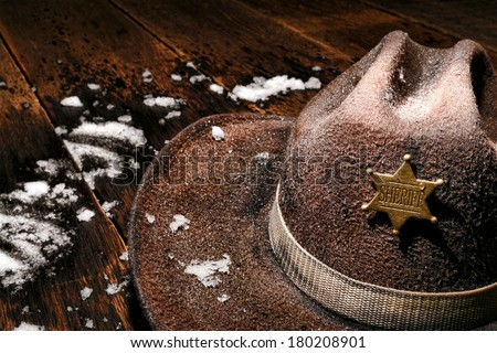American West wet and worn vintage lawman cowboy hat with law enforcement sheriff star badge on antique wood plank table with fresh winter snow after law enforcement cold patrol on western frontier  - stock photo