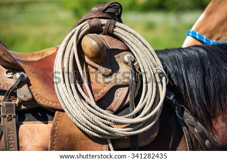 American West working rancher and cowboy rope, saddle, tack, and lasso hanging on to an authentic used and worn brown leather western saddle on a real working horse. - stock photo