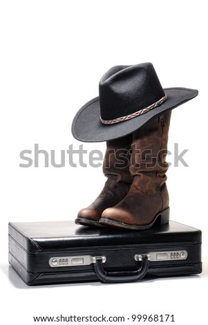 American Western Texas style business with black cowboy hat atop traditional brown leather boots on a businessman briefcase over white - stock photo