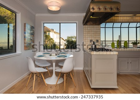 American white kitchen with wooden floor and breakfast nook and view window - home interior design. - stock photo