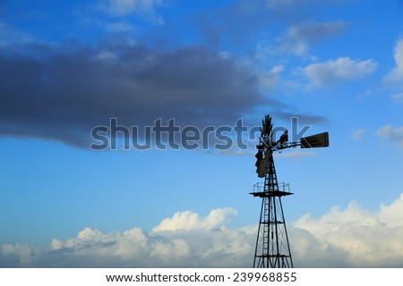 American windmill and a blue sky with different clouds. - stock photo