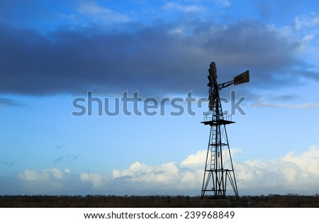 American windmill in open farmland, and a sky with different clouds.