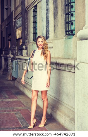 American Woman Fashion in New York. Wearing sleeveless antique white dress with doll collar, high heels, shoulder carrying bag, a lady with long curly blonde hair standing by vintage wall on street.