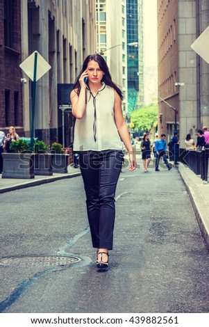 American Woman traveling in New York in summer, wearing white collarless sleeveless shirt, black pants, high heels, walking on vintage narrow street, talking on cell phone. Instagram filtered effect.