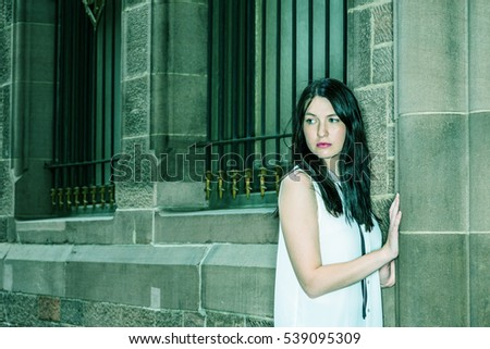 American Woman with long black hair, wearing white sleeveless shirt, standing by vintage wall with widows on street in New York, turning around, looking down, sad, thinking. Color filtered effect